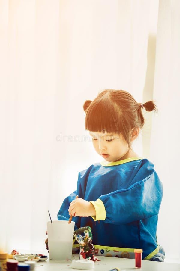 Retrato de uma menina bonito que joga messily com pinturas imagens de stock royalty free