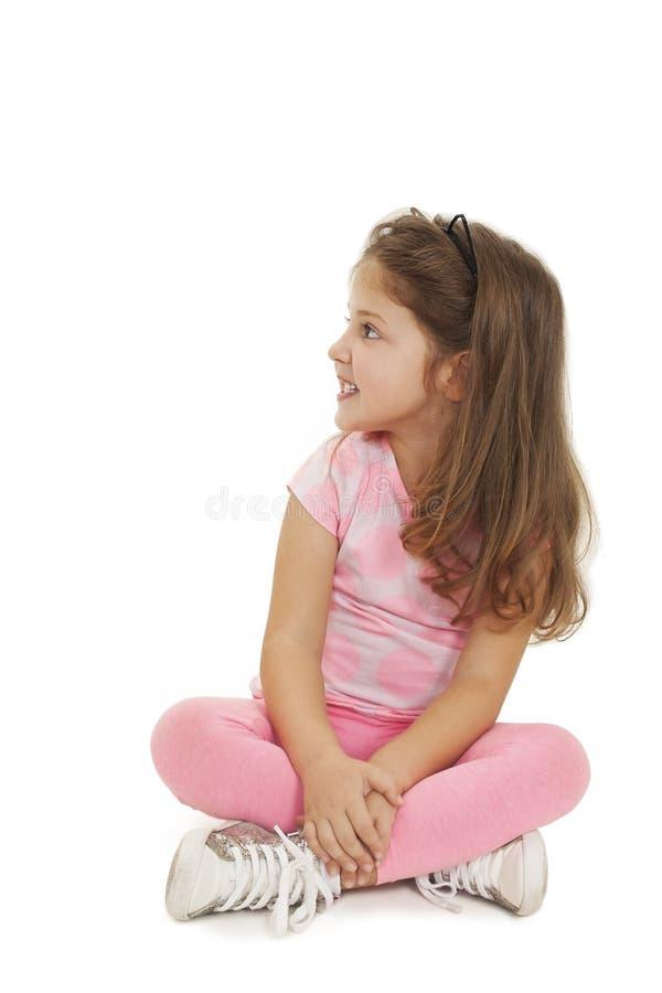Retrato de uma menina bonito que senta-se no assoalho, olhando acima fotos de stock royalty free