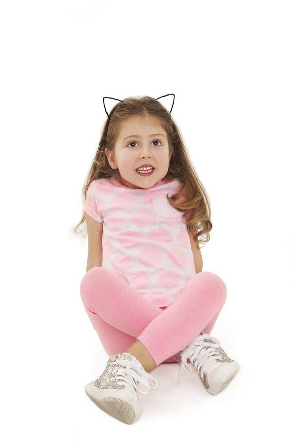 Retrato de uma menina bonito que senta-se no assoalho, olhando acima fotografia de stock royalty free