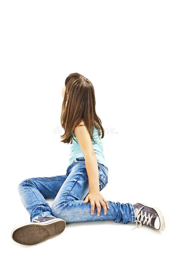 Retrato de uma menina bonito que senta-se no assoalho, olhando acima na parede foto de stock
