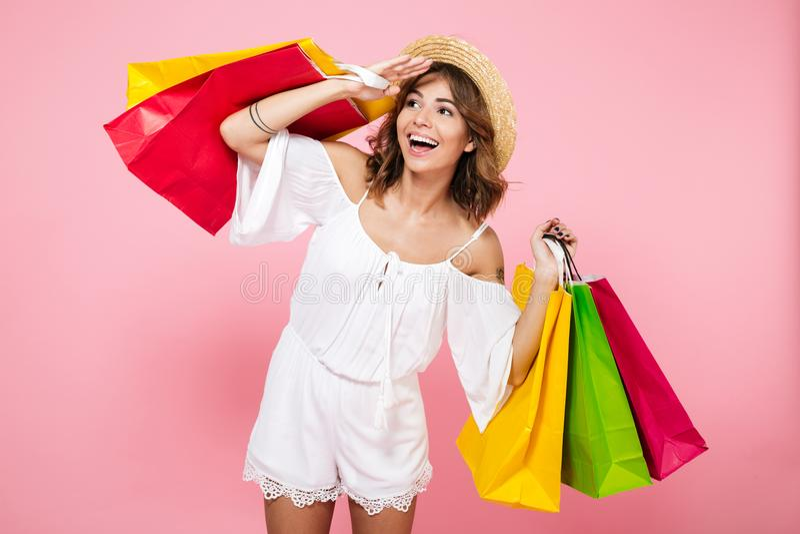 Retrato de uma menina de cabelo marrom que guarda sacos de compras coloridos imagens de stock royalty free