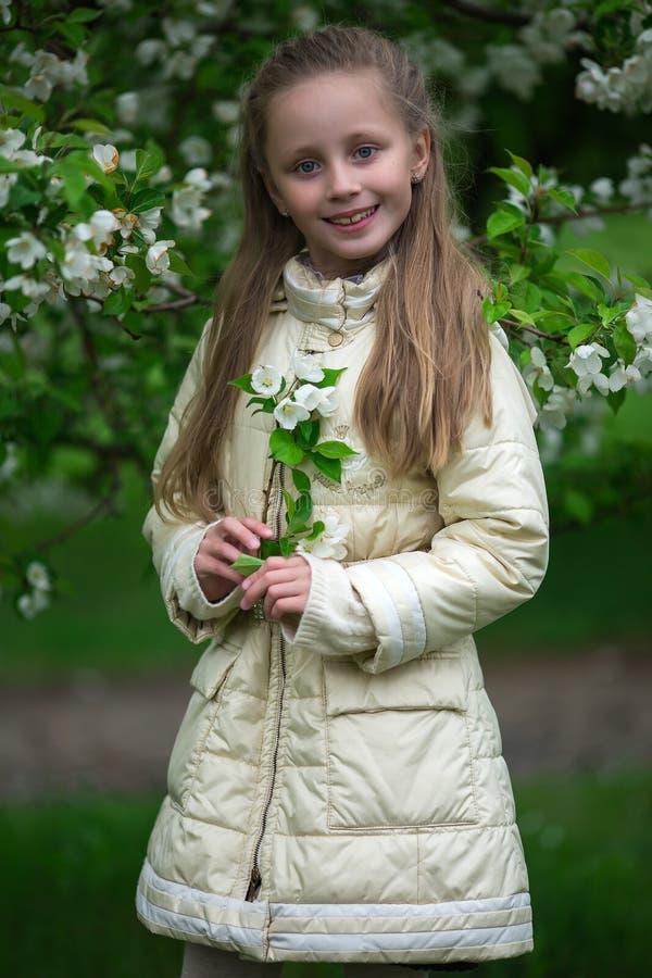 Retrato de uma menina de cabelos compridos nova bonita Criança adorável que tem o divertimento no jardim da cereja da flor no dia fotografia de stock