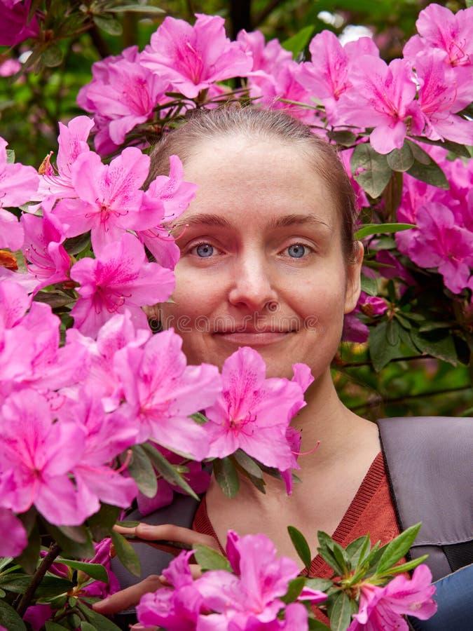Retrato de uma menina cercada por flores cor-de-rosa do rododendro imagens de stock
