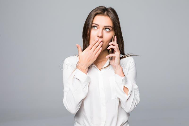 Retrato de uma menina chocada surpreendida na camiseta que fala no telefone celular e que olha isolada afastado sobre o fundo cin foto de stock