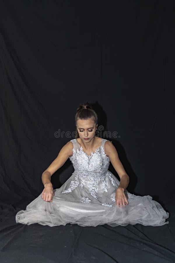 Retrato de uma menina com cabelo longo e os olhos verdes em um vestido de casamento que senta-se no assoalho Fundo preto foto de stock