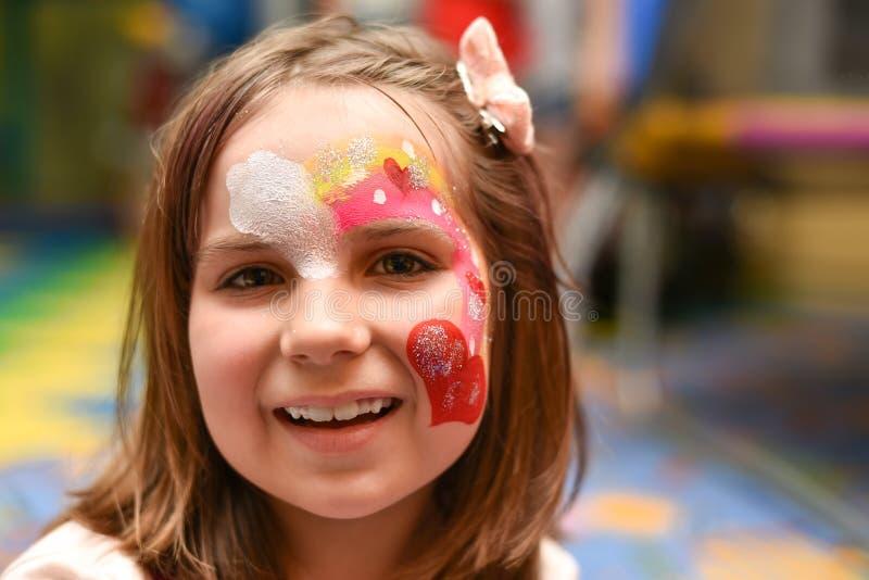 Retrato de uma menina com uma cara pintada fotos de stock