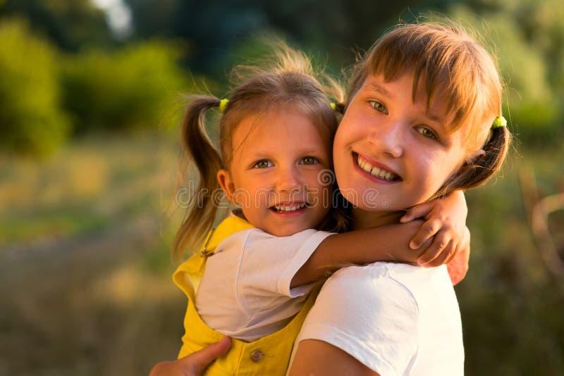 Retrato de uma menina com a irmã mais idosa adolescente na natureza foto de stock royalty free