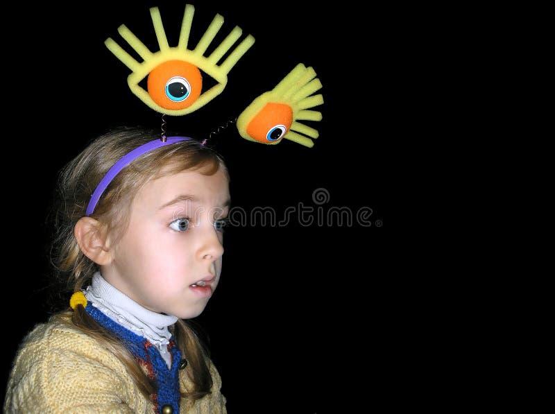 Retrato de uma menina com olhos grandes em um fundo preto fotografia de stock