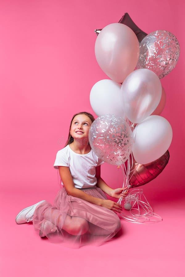 Retrato de uma menina com os balões no estúdio, em um fundo cor-de-rosa, close-up imagens de stock