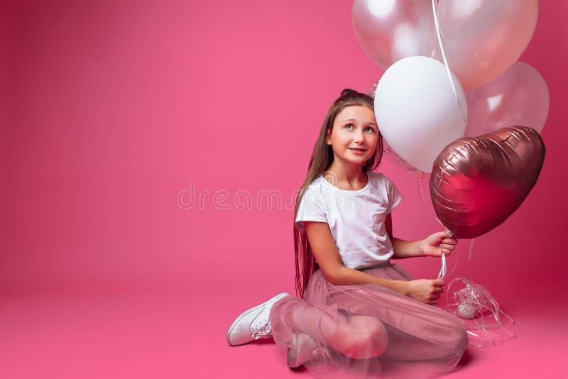 Retrato de uma menina com os balões no estúdio, em um fundo cor-de-rosa, close-up foto de stock royalty free