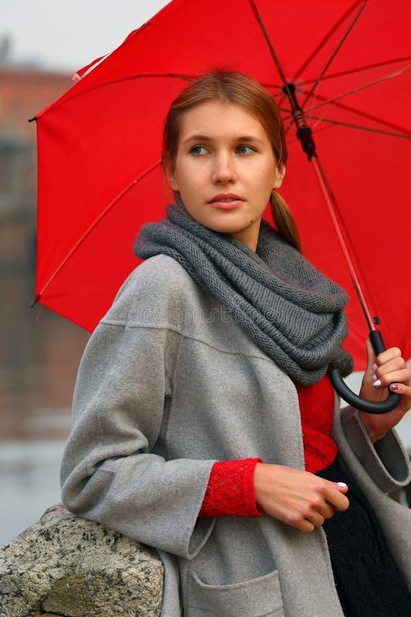 Retrato de uma menina com um guarda-chuva vermelho fotos de stock royalty free
