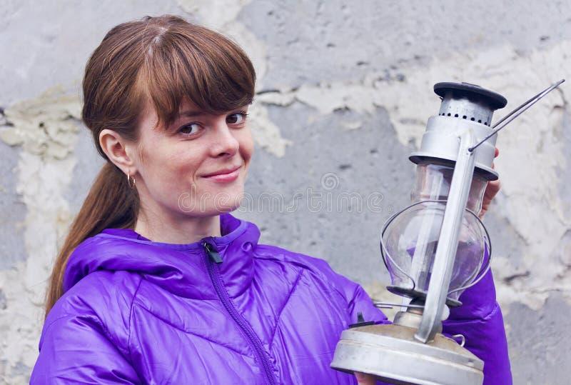 Retrato de uma menina com uma lâmpada de querosene em suas mãos fotos de stock