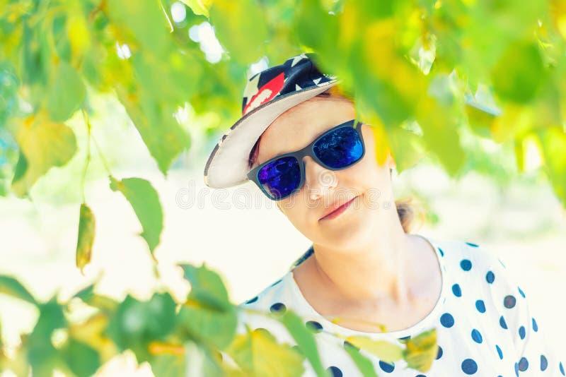 Retrato de uma menina com vidros e um tampão, uma menina à moda e bonita nova nos óculos de sol no parque imagem de stock