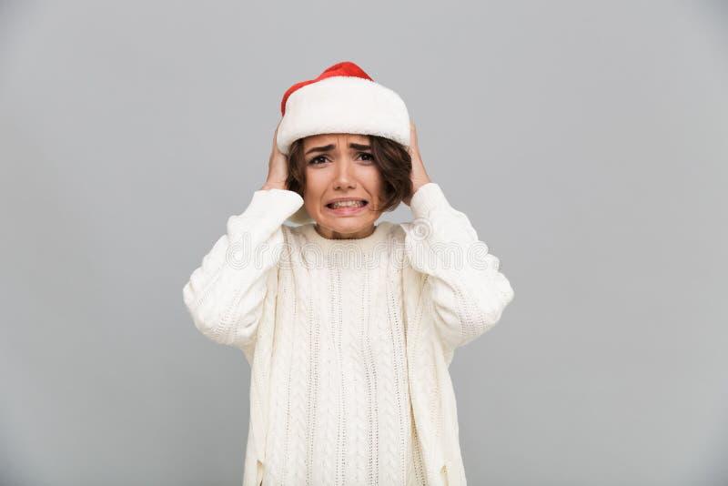 Retrato de uma menina confundida confusa no chapéu do Natal imagens de stock