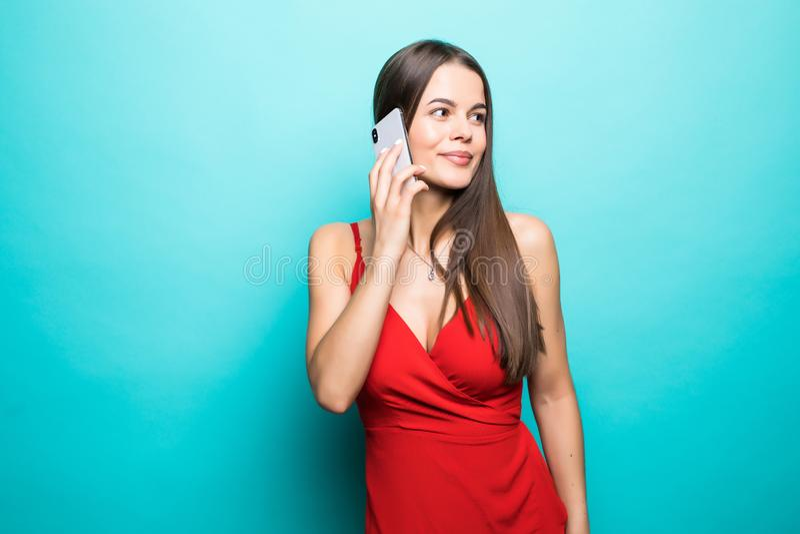 Retrato de uma menina consideravelmente alegre no vestido que fala no telefone celular isolado sobre o fundo azul imagem de stock