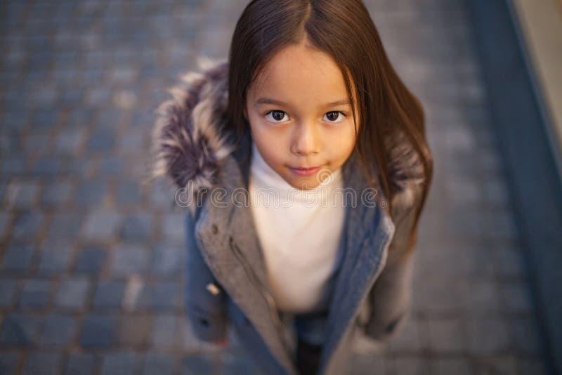 Retrato de uma menina da criança em um revestimento com uma capa da pele fotografia de stock