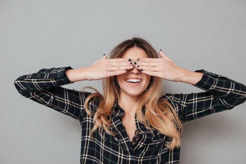 Retrato de uma menina de riso que cobre seus olhos com as mãos imagens de stock