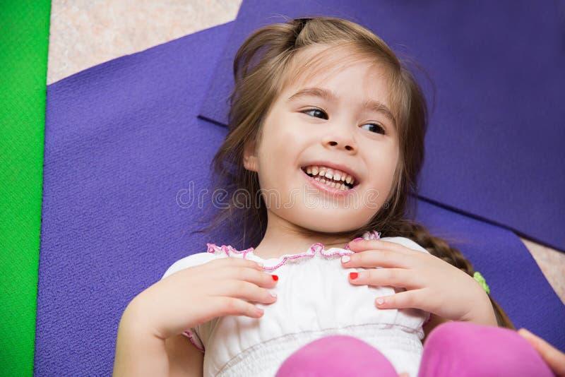 Retrato de uma menina de sorriso que encontra-se em uma esteira no gym fotos de stock royalty free