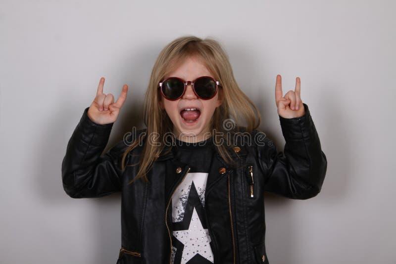 Retrato de uma menina do metal pesado com óculos de sol Menina bonito que faz um sinal do rocha-n-rolo foto de stock royalty free