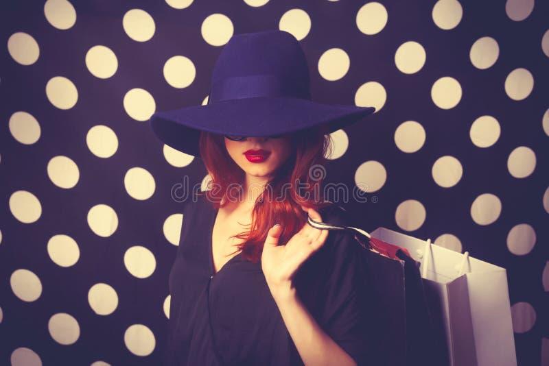 Retrato de uma menina do ruivo com sacos de compras imagens de stock