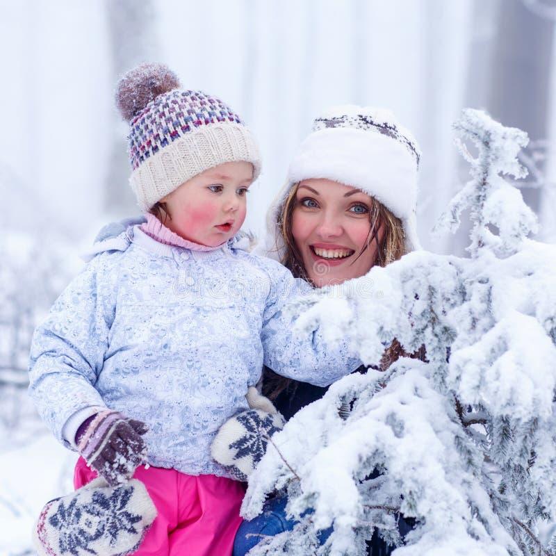 Retrato de uma menina e de uma mãe no chapéu do inverno em frentes da neve foto de stock