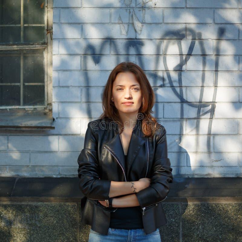 Retrato de uma menina em um casaco de cabedal que está no backgroun fotografia de stock royalty free
