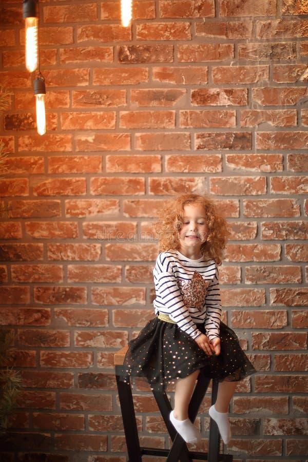 Retrato de uma menina em um fundo da parede de tijolo foto de stock