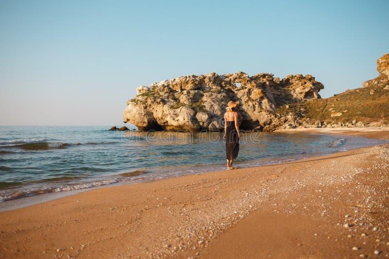 Retrato de uma menina em um vestido e em um chapéu pretos na praia fotos de stock royalty free