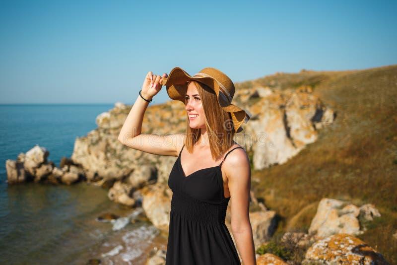Retrato de uma menina em um vestido e em um chapéu pretos na praia foto de stock