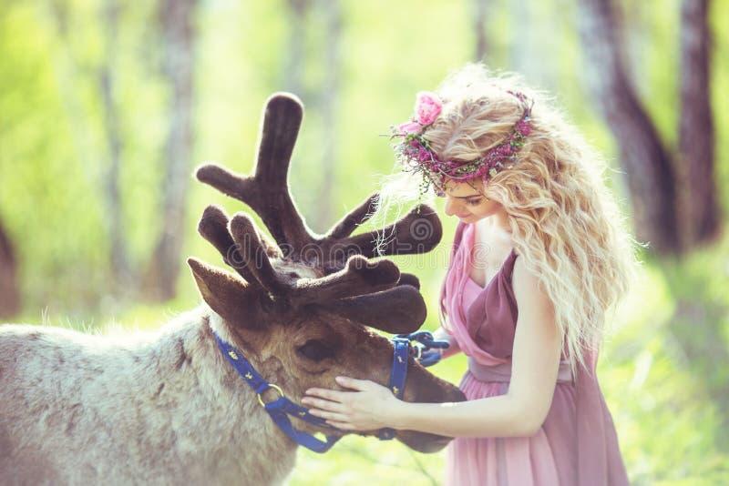 Retrato de uma menina em um vestido feericamente ao lado de uma rena imagem de stock