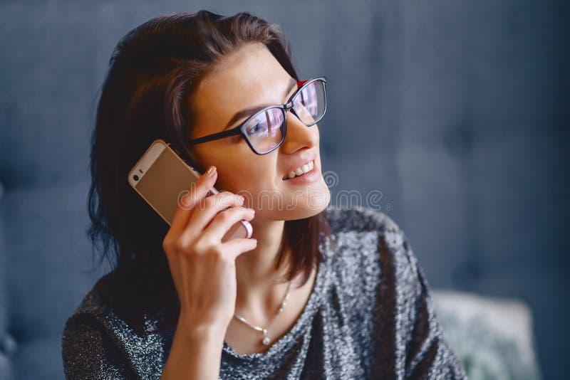 Retrato de uma menina encantador nos vidros com um telefone imagem de stock royalty free
