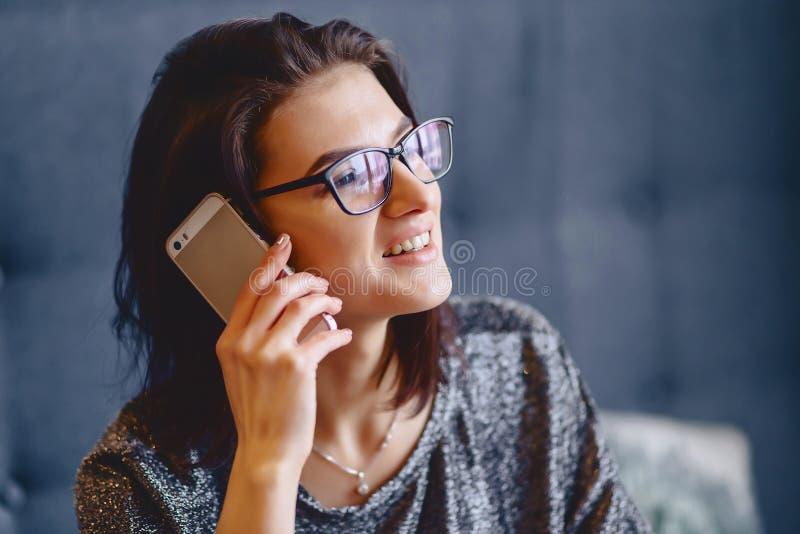Retrato de uma menina encantador nos vidros com um telefone fotos de stock
