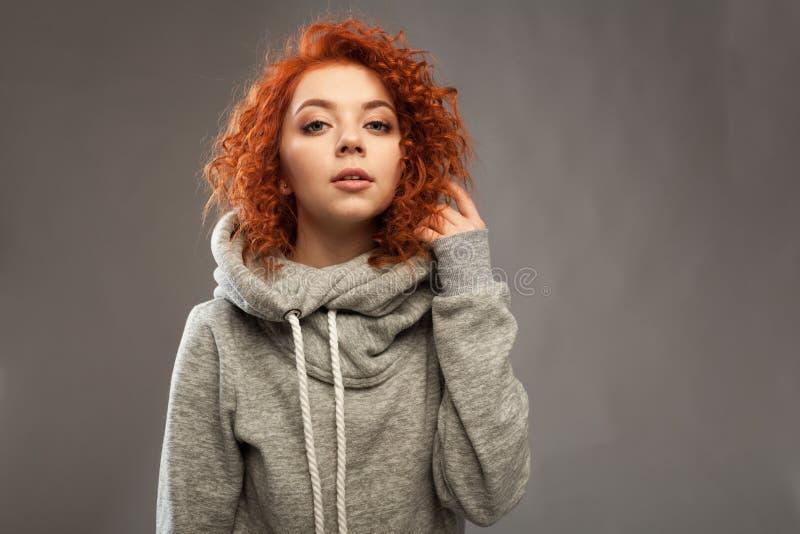 Retrato de uma menina encaracolado-de cabelo nova bonita com o cabelo vermelho impetuoso que olha a câmera em um fundo cinzento fotografia de stock