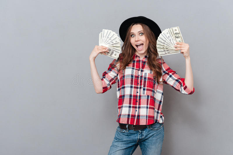 Retrato de uma menina entusiasmado feliz que guarda cédulas do dinheiro foto de stock