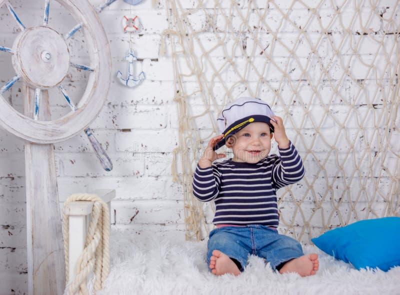 Retrato de uma menina europeia bonito e impertinente em uma roupa dos marinheiros no estúdio do estilo marinho em um fundo do bra fotos de stock royalty free