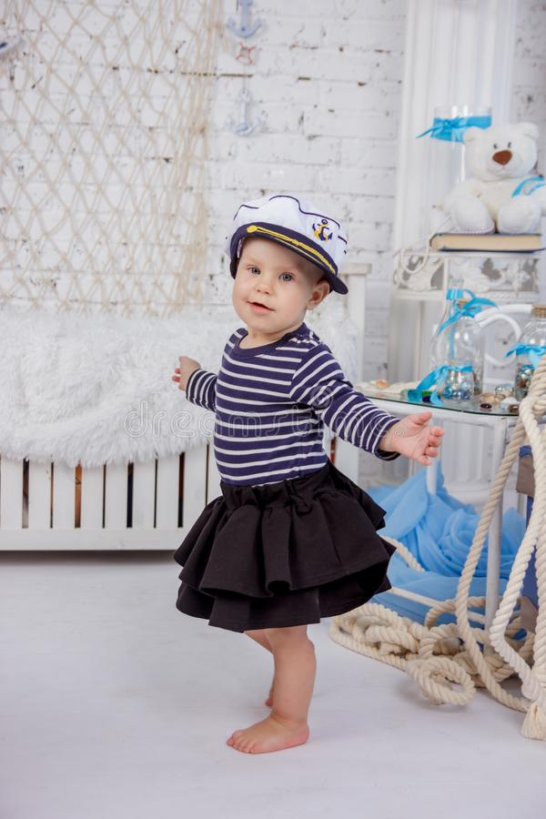 Retrato de uma menina europeia bonito e impertinente em uma roupa dos marinheiros no estúdio do estilo marinho em um fundo do bra fotos de stock