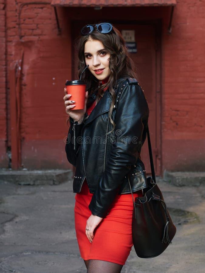 Retrato de uma menina europeia moreno encaracolado feliz nova vestida no casaco de cabedal vermelho do vestido que guarda o copo  imagem de stock