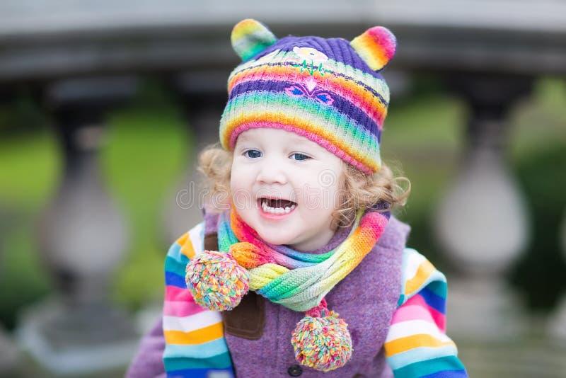 Retrato de uma menina feliz da criança no chapéu feito malha colorido fotografia de stock