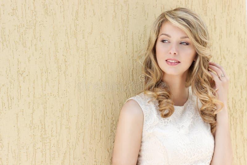 Retrato de uma menina feliz de sorriso 'sexy' bonita com os bordos completos grandes com cabelo louro em um vestido branco em um  foto de stock royalty free