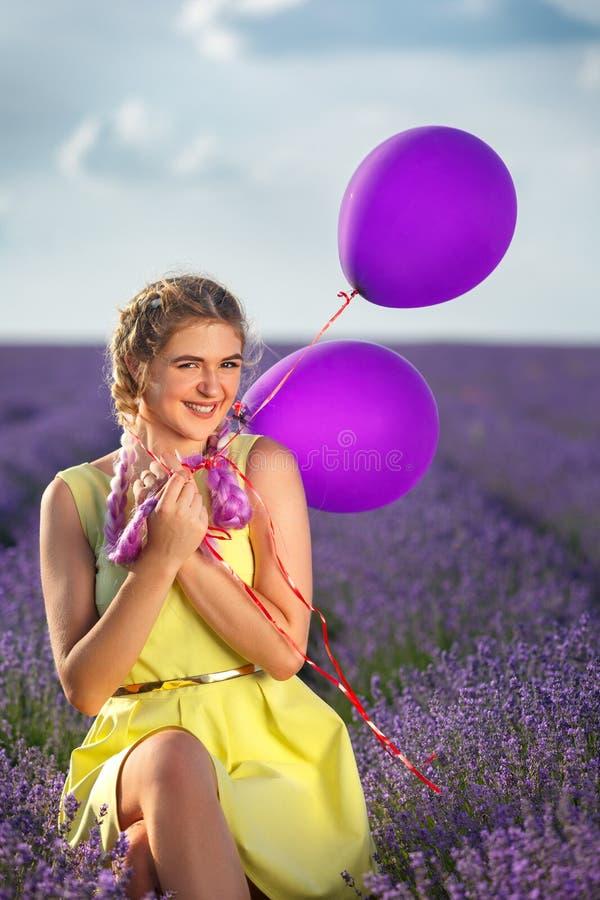 Retrato de uma menina feliz e alegre no vestido amarelo com balões em suas mãos No fundo, em um campo da alfazema e no céu azul fotografia de stock
