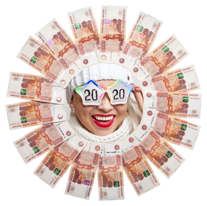 Retrato de uma menina feliz nos vidros com a inscrição 2020 no centro do círculo do dinheiro do russo imagens de stock