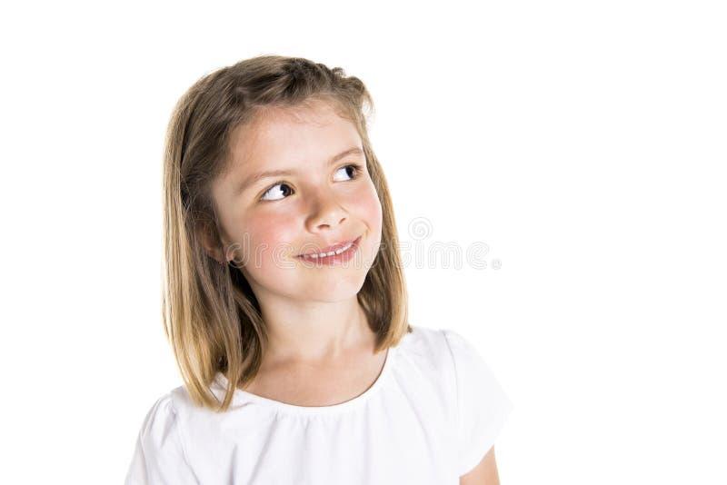 Retrato de uma menina idosa bonito de 7 anos isolada sobre o fundo branco pensativo fotografia de stock