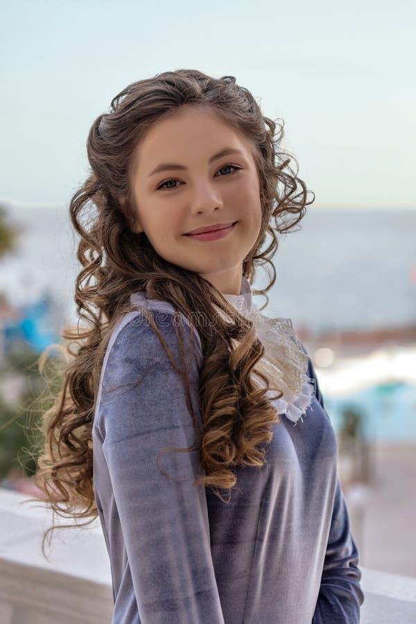Retrato de uma menina impertinente manhoso de sorriso com encrespadores em um vestido retro velho imagens de stock royalty free