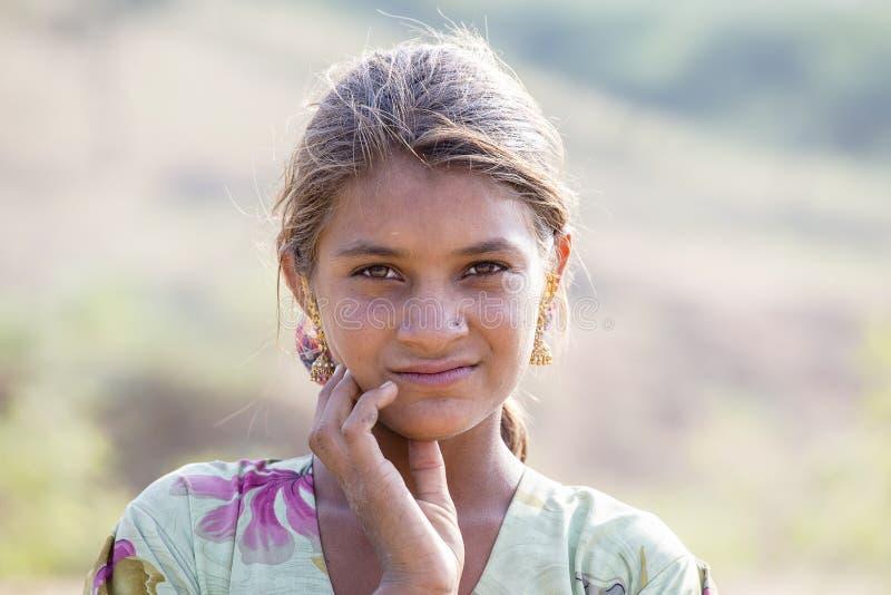 Retrato de uma menina indiana que participe nos camelos favoravelmente na cidade de Pushkar de Rajasthan, Índia imagem de stock