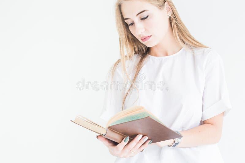 Retrato de uma menina loura à moda nova em um t-shirt branco e na calças de ganga que lê um livro em um fundo branco imagem de stock royalty free