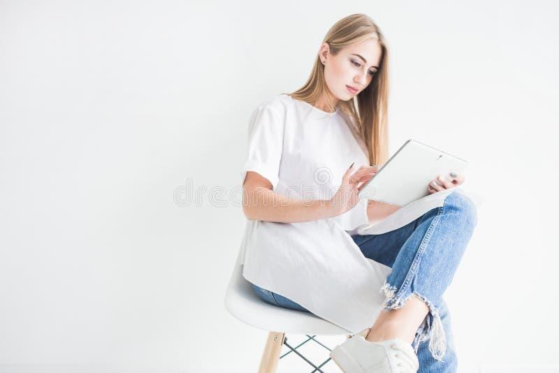 Retrato de uma menina loura à moda nova em um t-shirt branco e na calças de ganga usando uma tabuleta em um fundo branco foto de stock