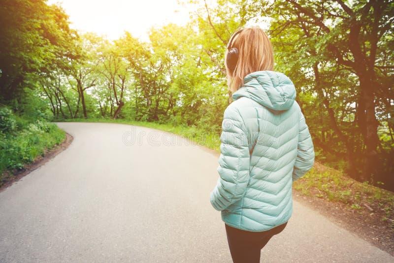 Retrato de uma menina loura atlética atrativa de volta à luz que corre abaixo do revestimento, fones de ouvido vestindo do blueto foto de stock