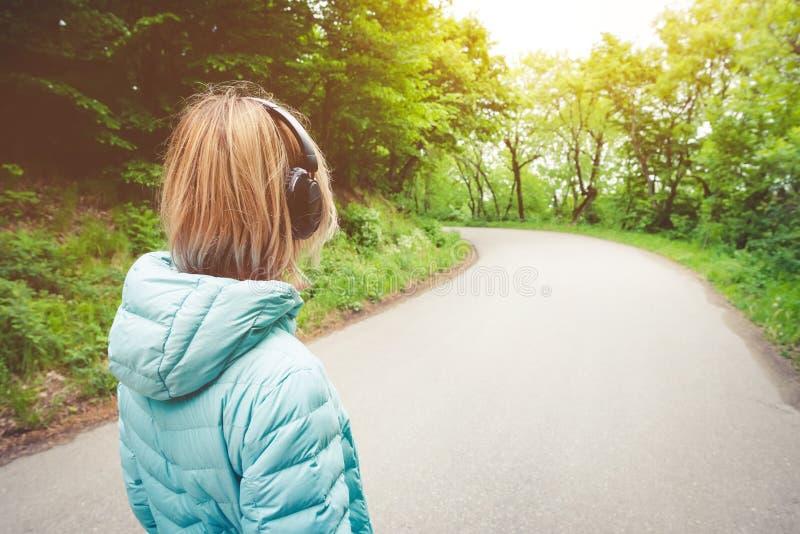 Retrato de uma menina loura atlética atrativa de volta à luz que corre abaixo do revestimento, fones de ouvido vestindo do blueto imagens de stock royalty free