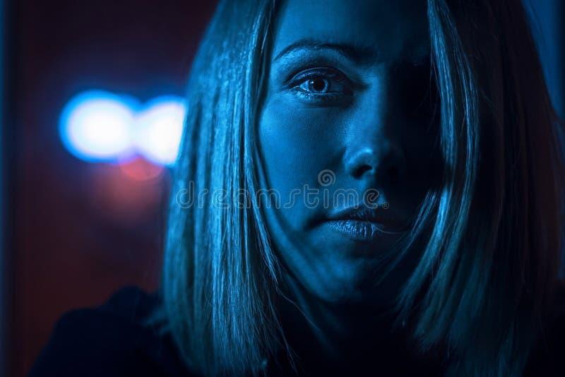 Retrato de uma menina loura bonita em uma janela no luar imagem de stock royalty free