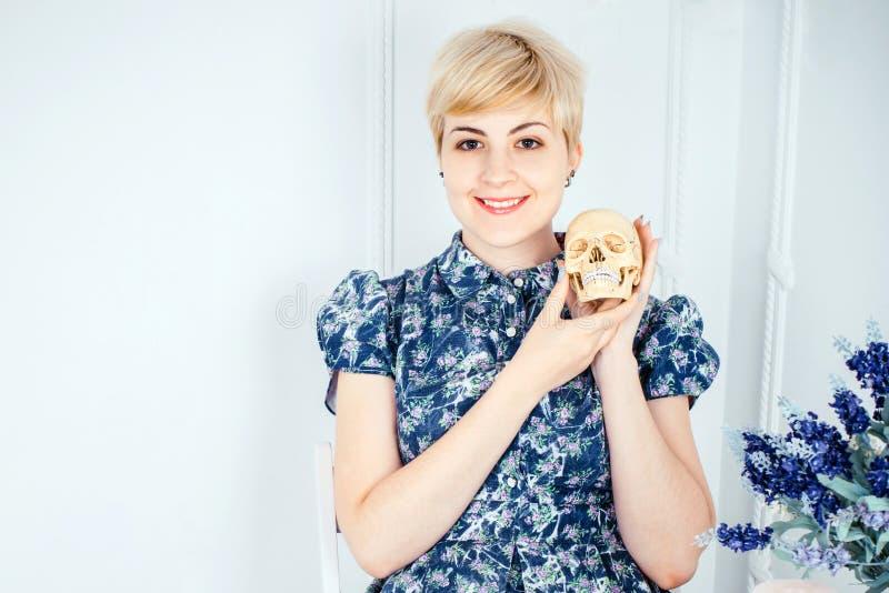 Retrato de uma menina loura bonita smilling que guarda o crânio imagens de stock